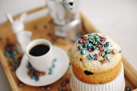 Easter cake sprinkled colored pearl coffee beans close up. Espresso maker moka pot and cup of coffee on the background