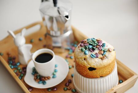 Easter still life. Coffee and cake. Espresso maker moka pot. White dishes, ceramic easter bunny. Colored coffee beans