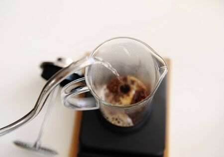 Brewing coffee in french press. Pouring hot water close up. Top view. White background