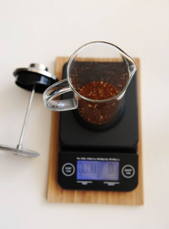 French press with ground coffee. On electronic timer scales. Top view. White background