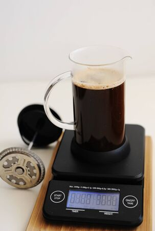 Brewing coffee in french press. On black electronic timer scales.