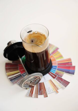 French press with ground coffee. On coffee Taster's Flavor Wheel. White background. Specialty coffee concept