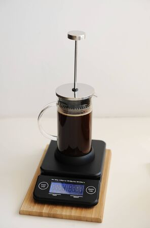 Brewing coffee in french press. Plunger not lowered. On black electronic timer scales. Specialty concept Zdjęcie Seryjne