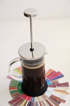 French press with ground coffee. On coffee Taster's Flavor Wheel. Plunger not lowered. White background. Specialty coffee concept Zdjęcie Seryjne