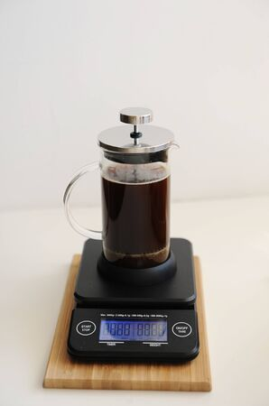 Brewing coffee in french press. Plunger lowered. On black electronic timer scales. Specialty concept Zdjęcie Seryjne