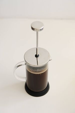 Brewing coffee in french press. Plunger not lowered. White background. Specialty concept