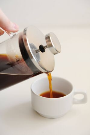 Pouring coffee from french press into white cup. White background. Close up Zdjęcie Seryjne