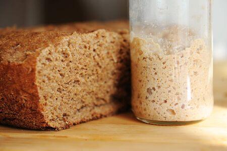 Sliced freshly baked homemade rye-wheat whole grain bread and rye sourdough in a glass jar. Closeup