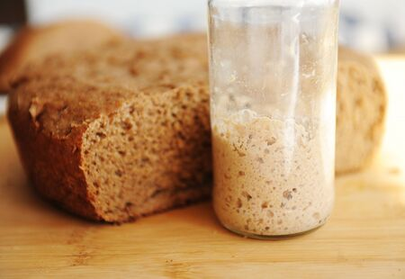 Freshly baked homemade rye-wheat whole grain bread and rye sourdough in a glass jar. Close up