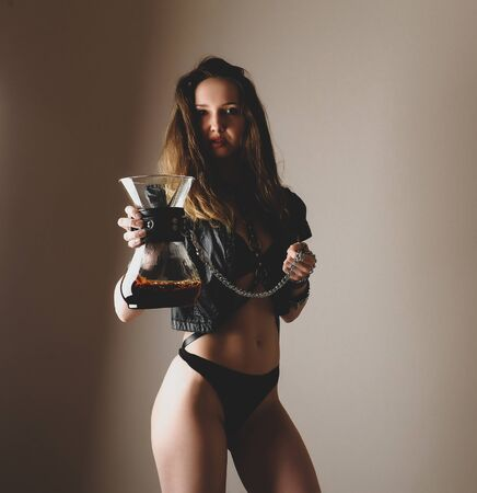 Beautiful sexy girl in black holds coffee decanter on leash chain. Passion, caffeine addiction, domination