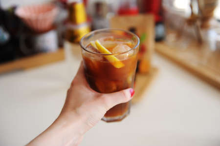 Espresso tonic with lemon slice in bid glass with ice in female hand close up. Summer recipe