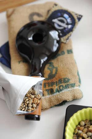 Home coffee roasting. Handle ceramic sample roaster. Green coffee beans