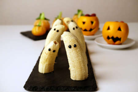 Healthy fruit Halloween treats. Banana ghosts, tangerines fake pumpkins, orange pumpkinhead Jacks