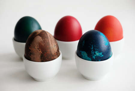 Easter dyed eggs on porcelain stands on a white background Stock Photo