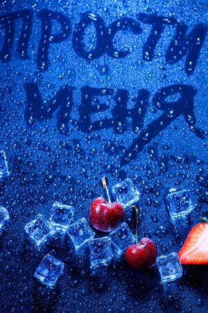 still life. pieces of ice, cherries, strawberries and the inscription in Russian