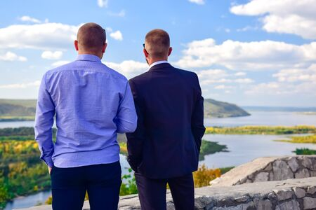 two men-businessman looking at the river from the observation deck on a clear day in early autumn 写真素材