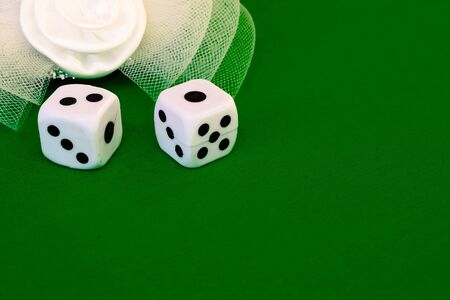 white dice on green cloth or tablecloth