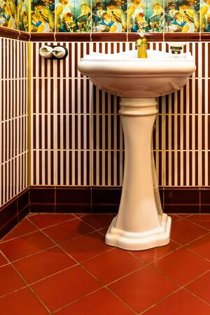 toilet room with sink finished with ceramic tiles