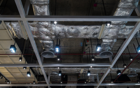 Ventilation system pipes on the ceiling of a modern factory plant building.