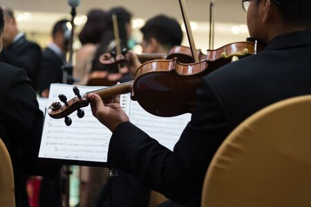 Symphony orchestra first violin section performing. Stock Photo