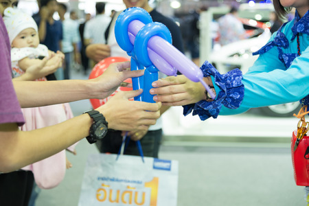 adults: Adults give balloons to children Stock Photo