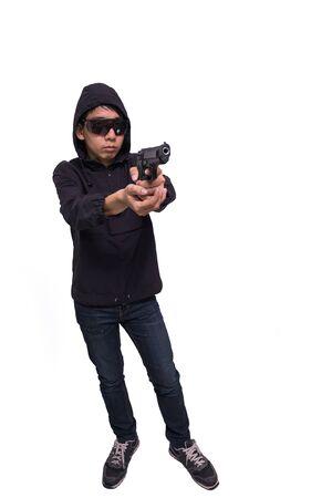 burglar or terrorist in black mask shooting with gun isolated on white background. Stock Photo