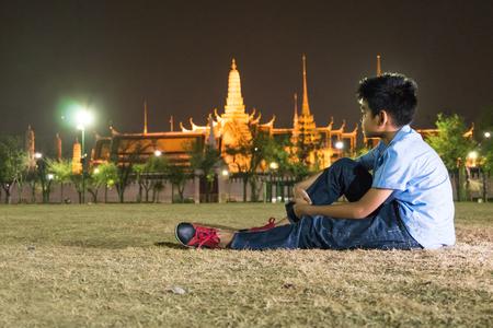 pra: Kid sitting on  grass near Wat Pra Kaew.
