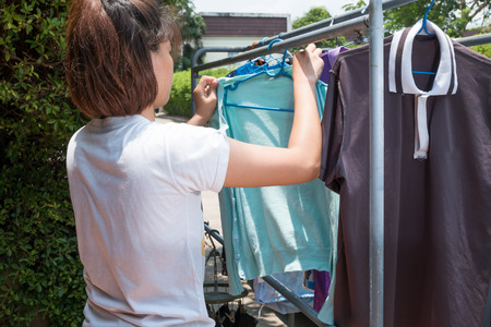 Woman hanging clothes on dryer at home.