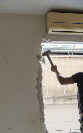 hitting a wall: builder hitting a wall with a sledge hammer