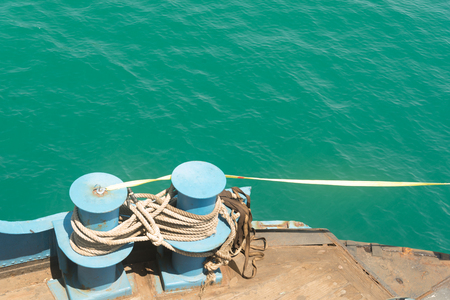 Mooring rope and bollard on sea water and coast background Stock Photo