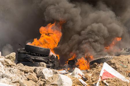 Brandende rubberbanden die grote zwarte rook en vervuiling creëren.