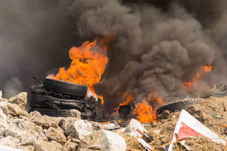 Burning rubber tires creating big black smoke and pollution.