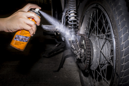 Cleaning and oiling a motorcycle chain and gear with oil Spray