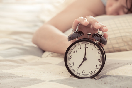 Woman turning off the alarm clock Standard-Bild