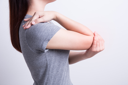 Asian woman with elbow pain on white background Stock Photo