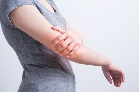 Asian woman with elbow pain on white background Stockfoto