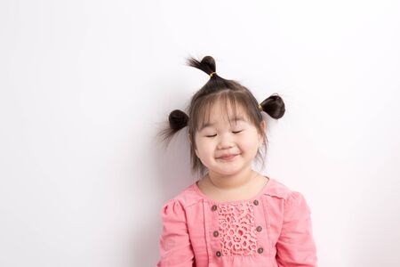 close your eyes: Asian girl smiling on white background,Close your eyes and smile