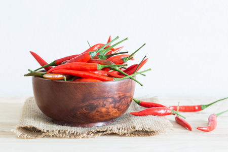 Red chili in a wooden bowl on a wooden table