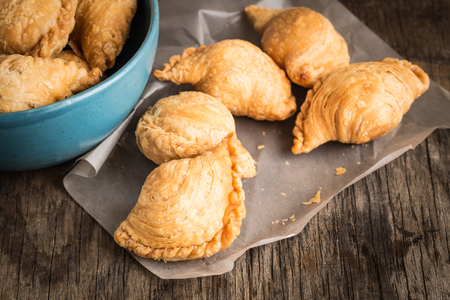 Curry puff on paper on old wooden table Stockfoto