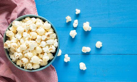 popcorn in bowl on blue wooden background,top view