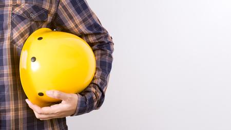 Ingeniero de la celebración de un casco sobre un fondo blanco. Foto de archivo - 80492872