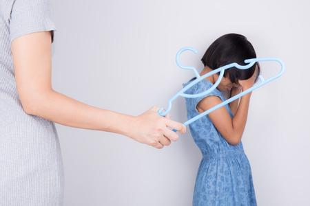 母は、ハンガーと押すことで娘を処罰です。家庭内暴力の概念
