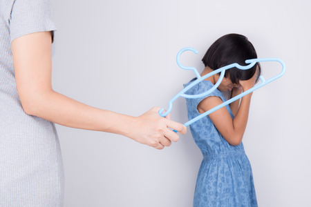 Mother is punishing daughter by hitting with a hanger.Family violence concept Stock Photo