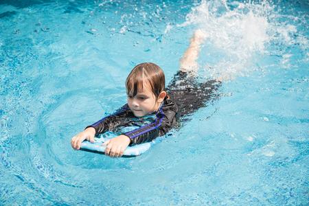 屋外スイミング プールで遊んでいる少年の子供が泳げるようになります。