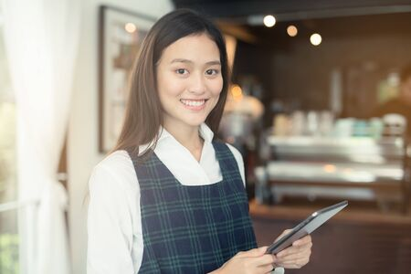 Asian woman barista smiling with tablet in her hand,Female employees are taking orders from online customers.,Warm photos at the coffee shop