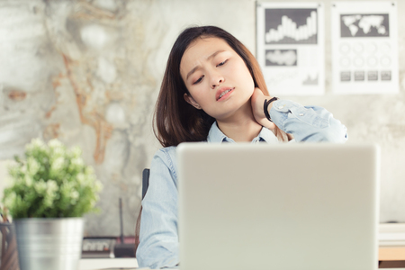 アジアの女性事務所に仕事から首の痛みがあります。ノートブック、オフィス症候群から病気の概念の使用から若い女性疲労