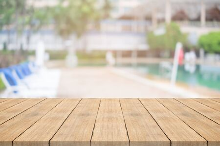 Empty wooden table in front with blurred background of swimming pool Stockfoto