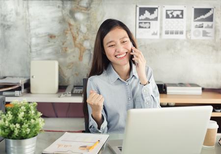 新世代ビジネス女性のスマート フォンを使用してアジアの女性は、オフィスで働く幸せ 写真素材