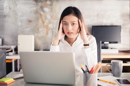 若いビジネス人に苦しんでいる頭痛、アジア女性ストレスの多い働く長い時間、オフィス症候群の概念のためのノート