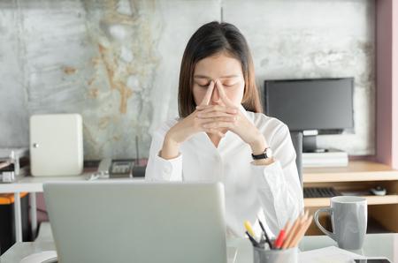 若いビジネスマンは頭痛に苦しんでいる、アジアの女性は長い間ノートを使って働くストレス、オフィス症候群の概念 写真素材